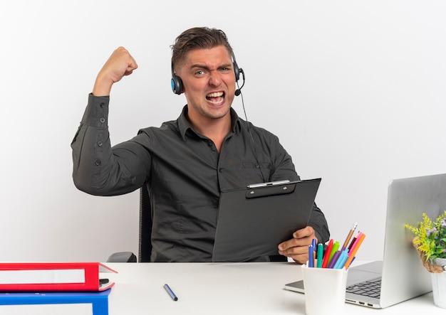 ヘッドフォンで若いうれしそうな金髪のサラリーマンの男は、コピースペースと白い背景で隔離の上げられた握りこぶしでクリップボードを保持ラップトップを使用してオフィスツールで机に座っています