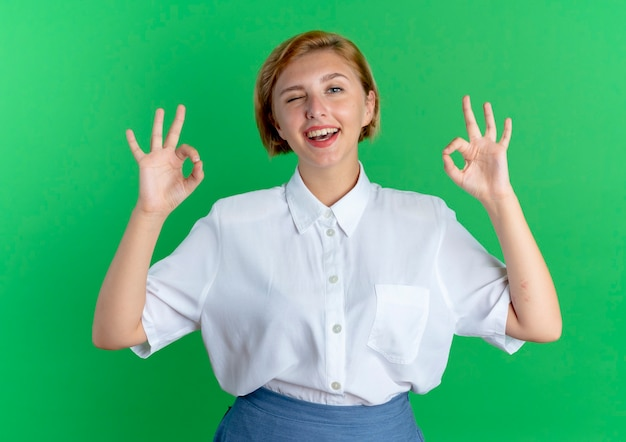 Young joyful blonde russian girl blinks eye gesturing ok sign with two hands isolated on green background with copy space