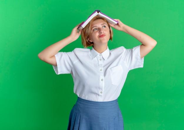 La giovane ragazza russa bionda allegra tiene il libro sopra la testa isolata su fondo verde con lo spazio della copia