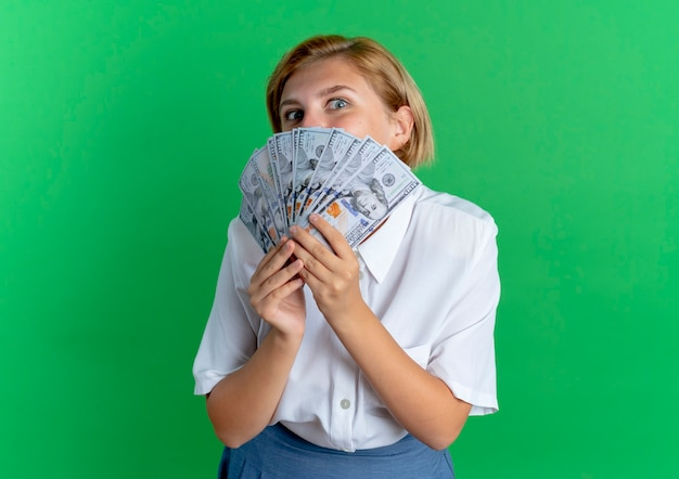 Young joyful blonde russian girl holds and looks over money isolated on green background with copy space