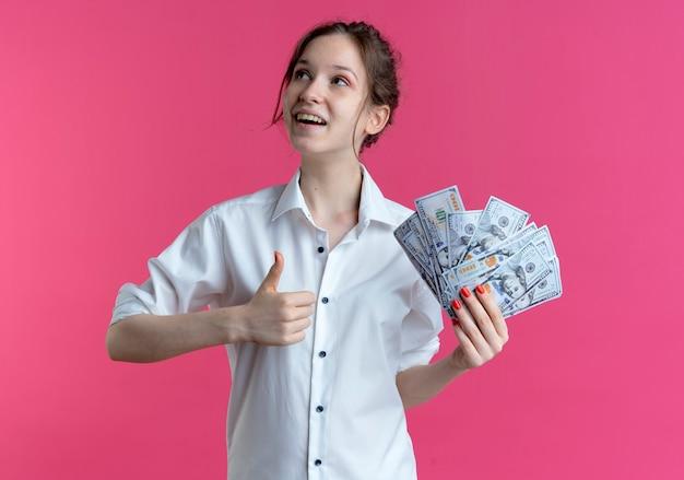 若いうれしそうな金髪のロシアの女の子は、コピースペースでピンクの側を見てお金と親指を保持します