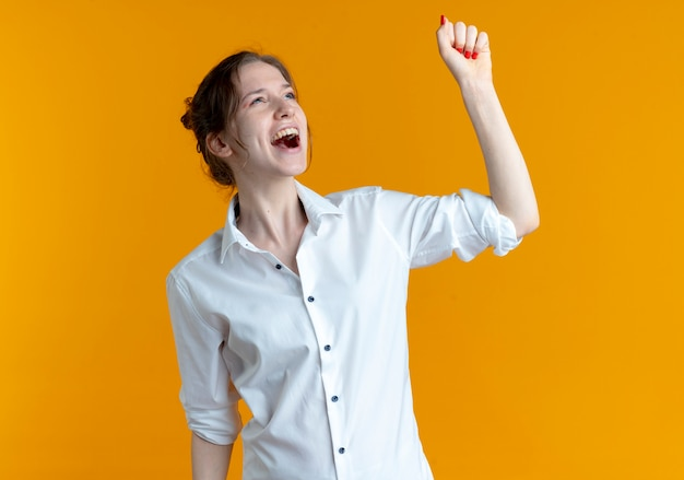 Young joyful blonde russian girl raises fist up looking at side isolated on orange space with copy space