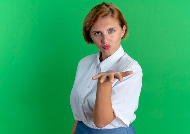 Молодая радостная русская блондинка стоит боком и отправляет поцелуи рукой, изолированной на зеленом фоне с копией пространства