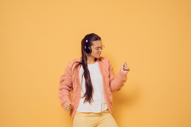 Young joyful brunette in glasses and headphones on her head  dressed in pink sweater white blouse and yellow pants enjoying the music and dancing over yellow background with copy space.