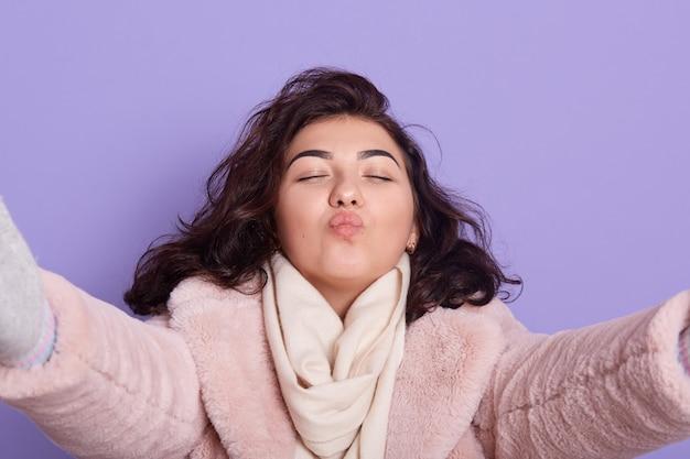 Young joyful brunette woman holding taking selfie self portrait of herself