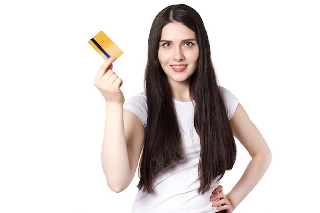 Молодая радостная брюнетка в белой футболке демонстрирует свою кредитную карту золотого банка для макета