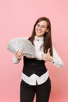 Young joyful business woman in glasses holding bundle lots of dollars, cash money and showing thumb up isolated on pink background. lady boss. achievement career wealth. copy space for advertisement.