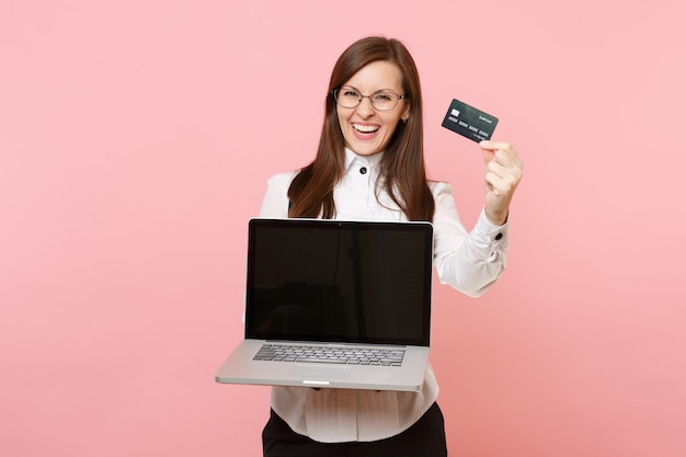 Young joyful business woman in glasses holding credit card, laptop pc computer with blank empty screen isolated on pink background. lady boss. achievement career wealth. copy space for advertisement.