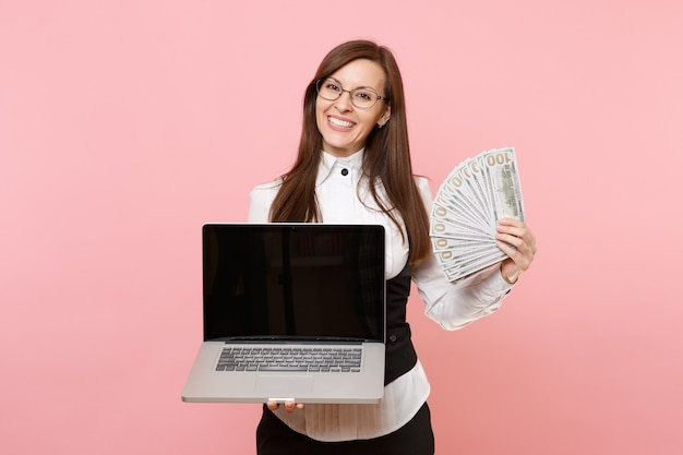 분홍색 배경에 격리된 빈 화면이 있는 많은 달러, 현금 및 노트북 컴퓨터를 들고 있는 젊은 즐거운 비즈니스 여성. 여사장님. 성취 경력 부입니다. 공간을 복사합니다.