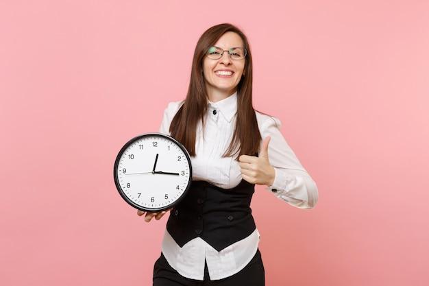 目覚まし時計を保持し、パステルピンクの背景に分離された親指を表示するスーツとメガネの若い楽しいビジネス女性。女上司。達成キャリア富の概念。広告用のスペースをコピーします。