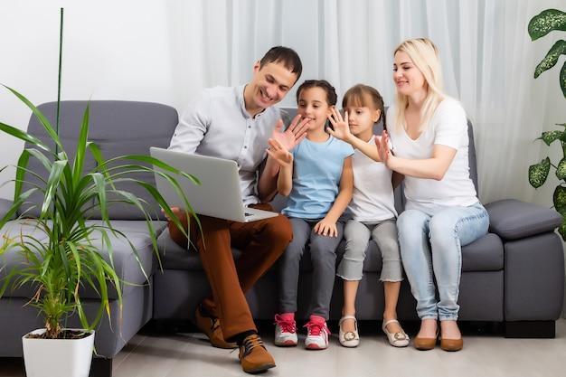 ソファに座って、タッチパッドで面白いビデオや漫画を見ている2人の子供とカップルの若い楽しいカジュアルな家族