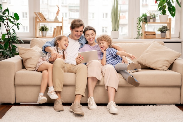 Young joyful casual family of two kids and couple sitting on sofa and watching funny video