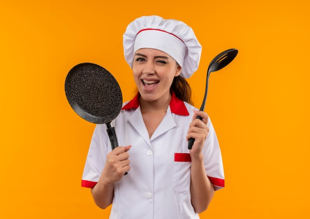 요리사 제복을 입은 젊은 즐거운 백인 요리사 소녀는 프라이팬을 보유하고 주걱은 복사 공간이있는 주황색 벽에 고립 된 눈을 깜박입니다.