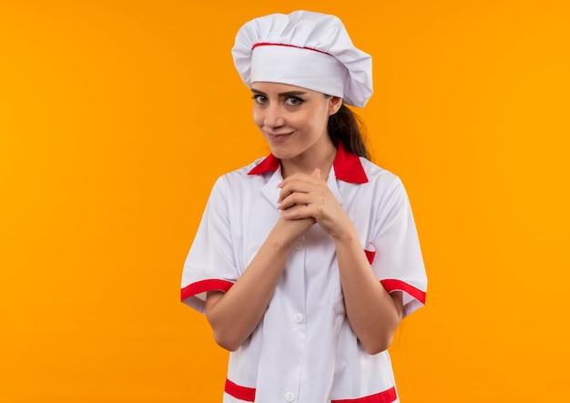 シェフの制服を着た若いうれしそうな白人料理人の女の子は、コピースペースでオレンジ色の壁に隔離された彼女の拳を保持します