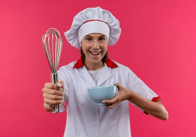 シェフの制服を着た若いうれしそうな白人料理人の女の子は、コピースペースとピンクのスペースに分離された泡立て器とボウルを保持します