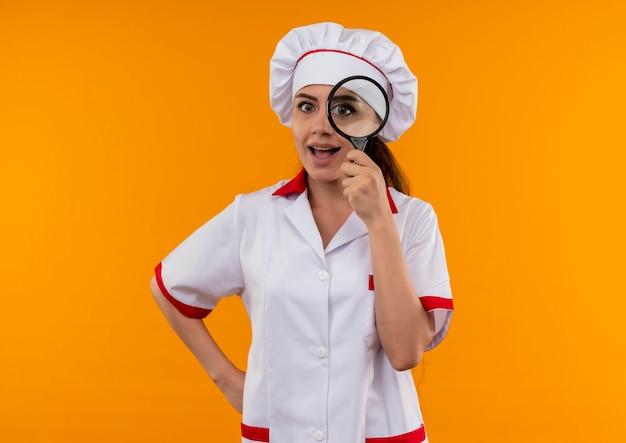 요리사 유니폼에 젊은 즐거운 백인 요리사 소녀는 돋보기 또는 복사 공간 오렌지 벽에 고립 된 부분 확대를 통해 보이는