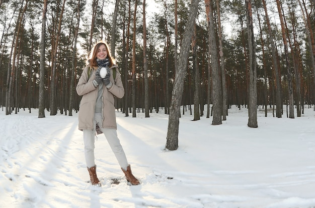A young and joyful caucasian girl in a brown coat holds a snowball in a snow-covered forest in winter. fisheye photo