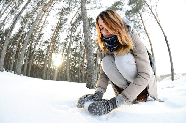 A young and joyful caucasian girl in a brown coat sculpts snow