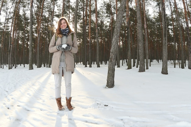 A young and joyful caucasian girl in a brown coat