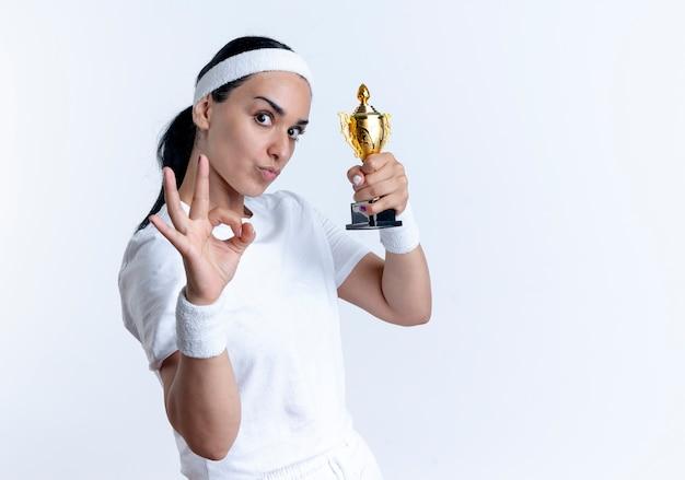 머리띠와 팔찌를 착용하는 젊은 즐거운 백인 스포티 한 여자는 승자 컵과 제스처 확인 손 기호 복사 공간이 흰색 공간에 고립 된 보유