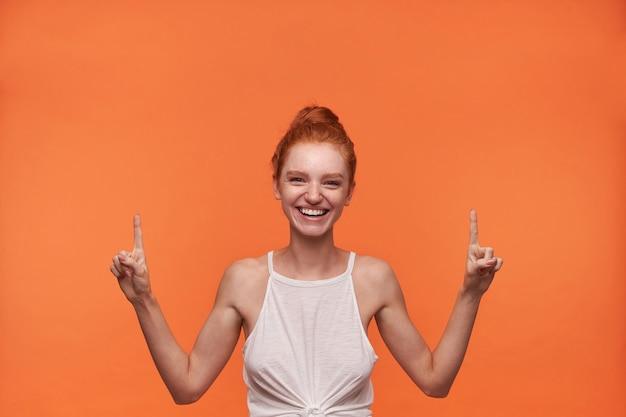 Giovane donna affascinante gioiosa con capelli volpi pettinati in ciambella in piedi su sfondo arancione, indossa un top casual bianco, alzando gli indici verso l'alto e sorridendo felicemente alla telecamera