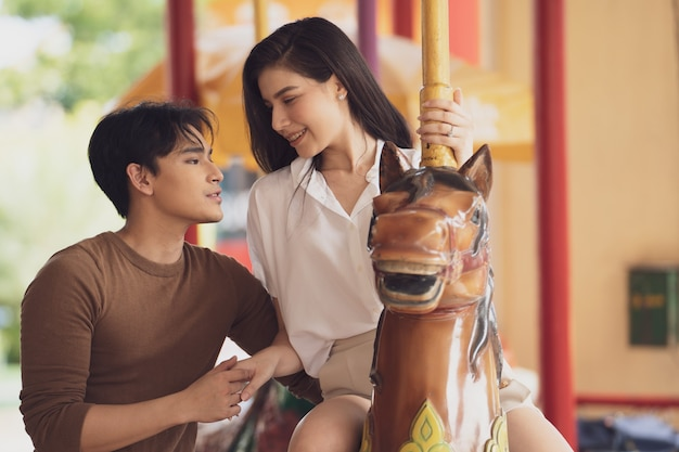 Young joyful couple man and woman riding on horse at carousel amusement park.