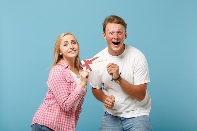 Giovane coppia gioiosa due amici ragazzo e donna in posa di magliette vuote vuote rosa bianche