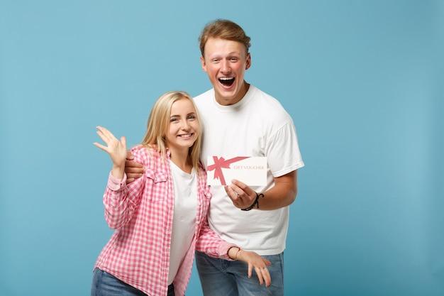 Giovane coppia gioiosa due amici ragazzo e donna in posa di magliette vuote rosa bianche