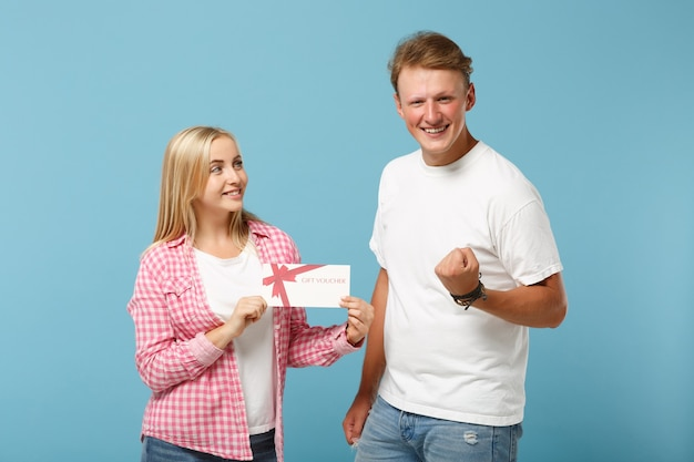 Young joyful couple two friends guy and woman in white pink t-shirts posing