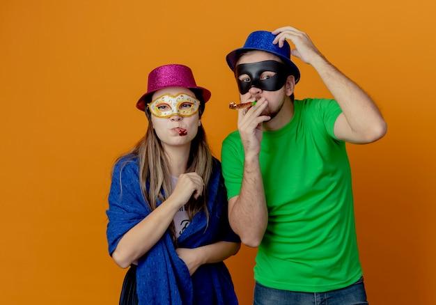 Молодая радостная пара в розовых и синих шляпах надевает маскарадные маски для глаз, дует в свисток и смотрит изолированно на оранжевой стене