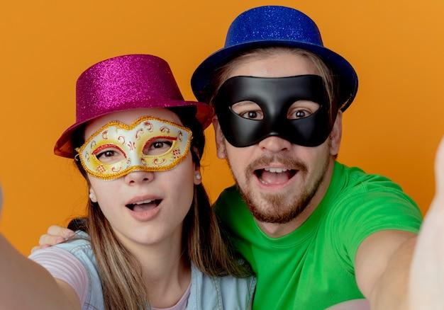 Молодая радостная пара в розовых и синих шляпах, надевших маскарадные маски для глаз, делает вид, что держится, и выглядит изолированной на оранжевой стене