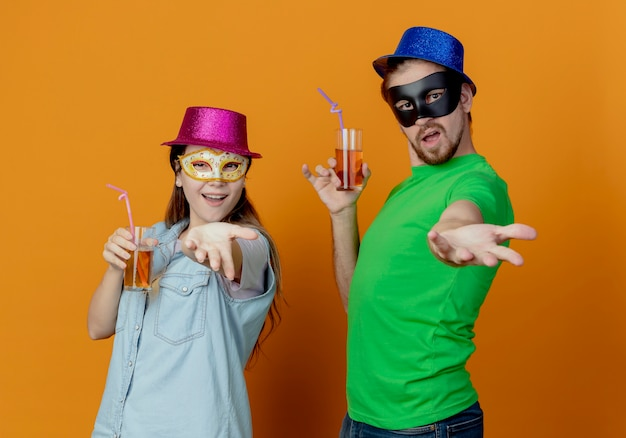 Young joyful couple wearing pink and blue hats put on masquerade eye masks holding glass of juice holds out hands isolated on orange wall