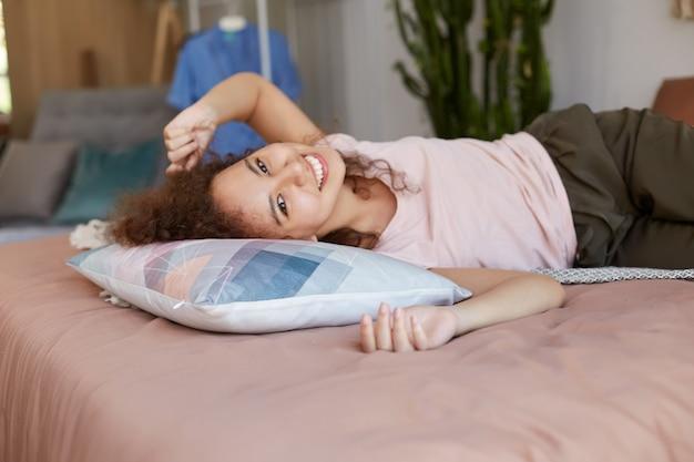 침대에 누워있는 젊은 즐거운 어두운 피부 여자는 집에서 화창한 날을 즐기고 넓게 웃고 행복해 보입니다.