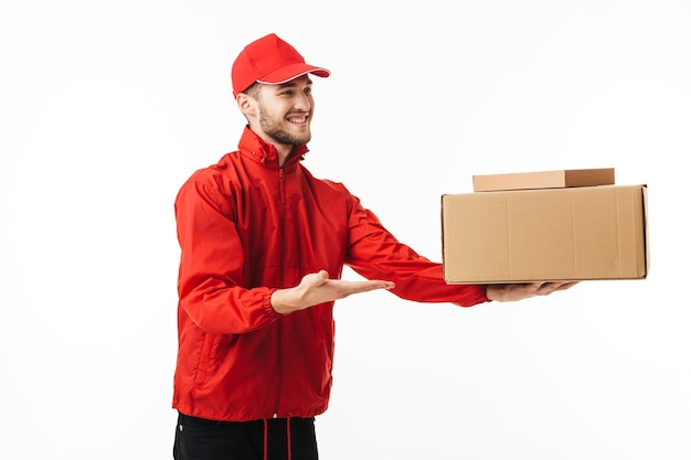 Young joyful delivery man in red cap and jacket happily giving package to customer