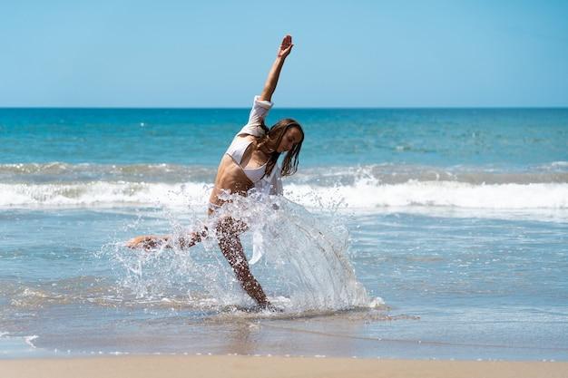 배경 휴가 및 여행 컨셉으로 바다와 함께 즐겁게 춤을 추면서 수영복과 흰색 셔츠를 입은 젊은 여성 댄서