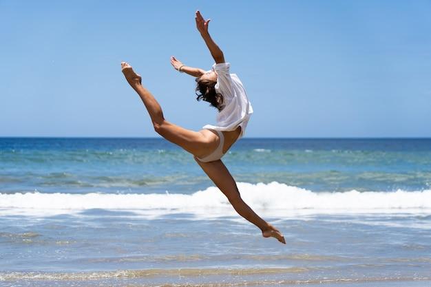 수영복과 흰색 셔츠를 입은 젊은 여성 댄서는 배경에서 바다와 함께 행복하게 점프합니다. 평온하고 행복 개념입니다.