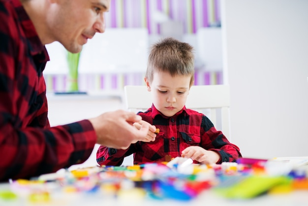 Young joyful focused father and son in the same shirt sitting in the bright living room playing.