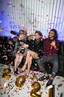 Молодые радостные друзья с пивом сидят на мягком диване во время новогодней вечеринки в ночном клубе