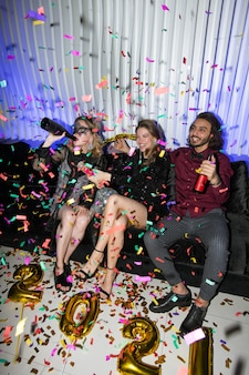 Young joyful friends with beer sitting on soft couch while having fun during new year party in the night club