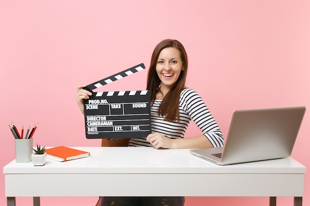 Young joyful girl holding classic black film making clapperboard working on project while sit at office with laptop isolated on pastel pink background. achievement business career concept. copy space.
