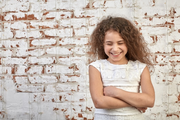 Young joyful girl smiling shyly over a brick wall crossed her arms relaxed