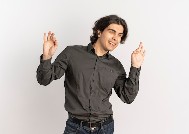 Young joyful handsome caucasian man gestures ok hand sign isolated on white background with copy space