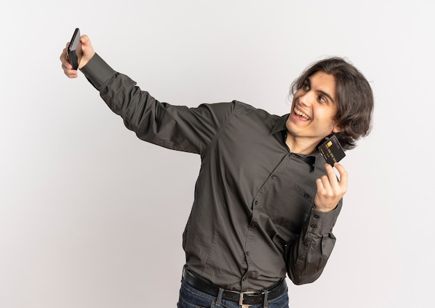 Young joyful handsome caucasian man holds credit card and looks at phone isolated on white background with copy space