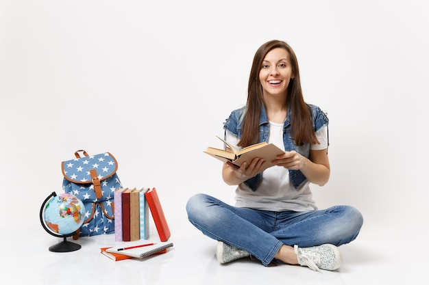Young joyful happy woman student in denim clothes holding book and reading sitting near globe, backpack, school books isolated