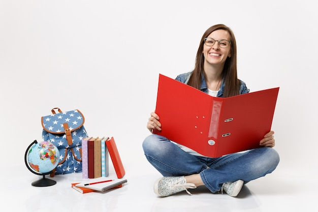 Young joyful happy woman student in glasses holding red folder for papers document sitting near globe backpack, school books