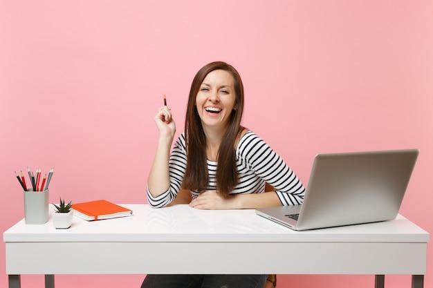 연필을 들고 캐주얼한 옷을 입은 젊고 즐거운 웃고 있는 여성은 현대적인 pc 노트북으로 흰색 책상에 앉아 일합니다