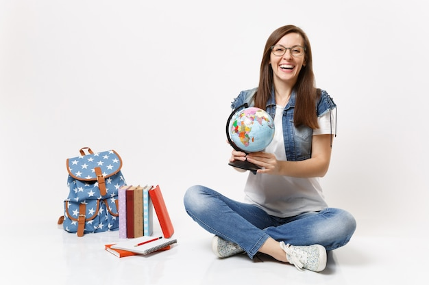 Young joyful laughing woman student in glasses holding world globe and learning geography sitting near backpack, school books isolated