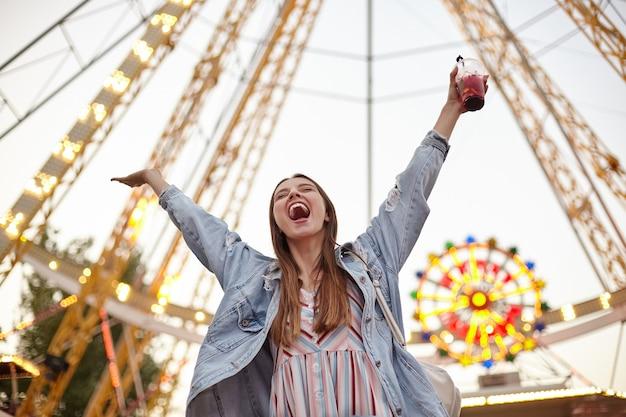 遊園地の観覧車の上に立って、手を上げて目を閉じて幸せに叫び、カジュアルな服を着て、若いうれしそうな長い髪のきれいな女性