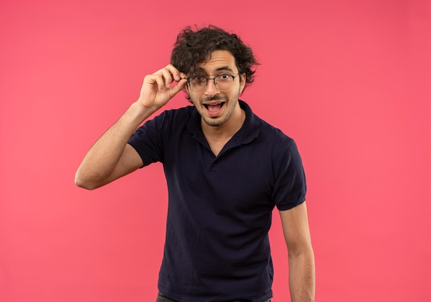 Young joyful man in black shirt with optical glasses holds glasses and looks isolated on pink wall