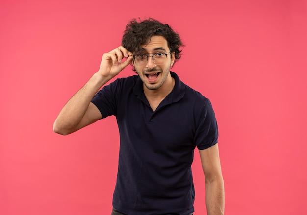 Giovane uomo gioioso in camicia nera con occhiali ottici tiene occhiali e sembra isolato sulla parete rosa